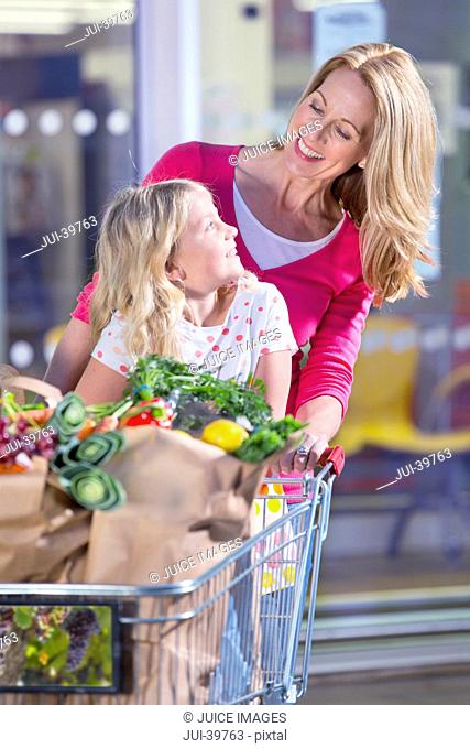 Mother Pushing Daughter In Trolley Outside Supermarket