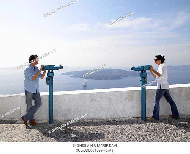 Couple looking through spyglasses