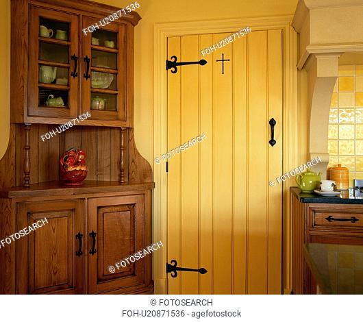 Chestnut-wood dresser beside yellow door in cottage kitchen