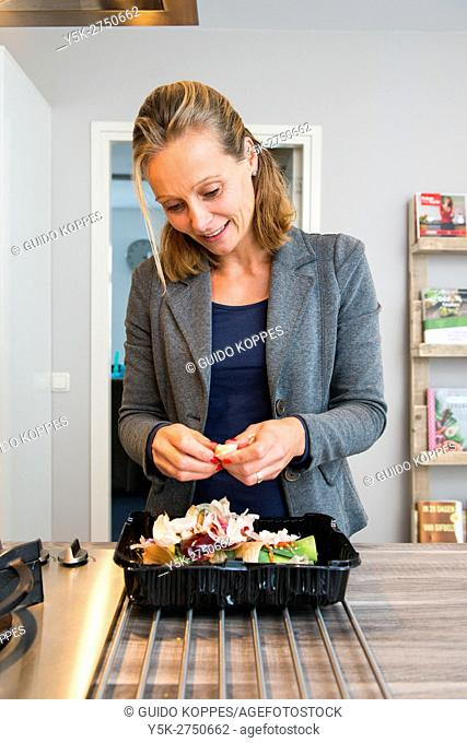 Kaatsheuvel, Netherlands. Mid adult woman cutting up garlic and groceries in preparation for a lasagna dish dinner