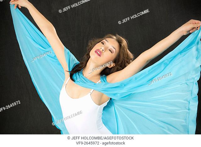 Beautiful young woman dancer in light blue cape and white leotard, half length with arms flung out, like wings, against black background, horizontal image