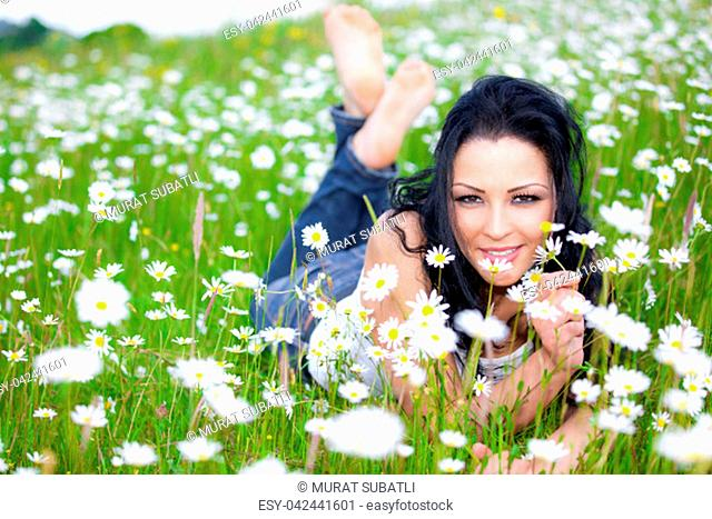 Beautiful woman laying on the flower filed