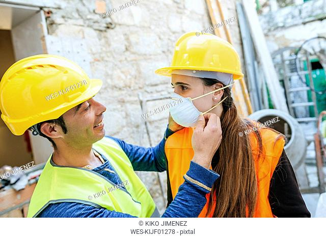 Man helping woman putting on dust mask on a construction site