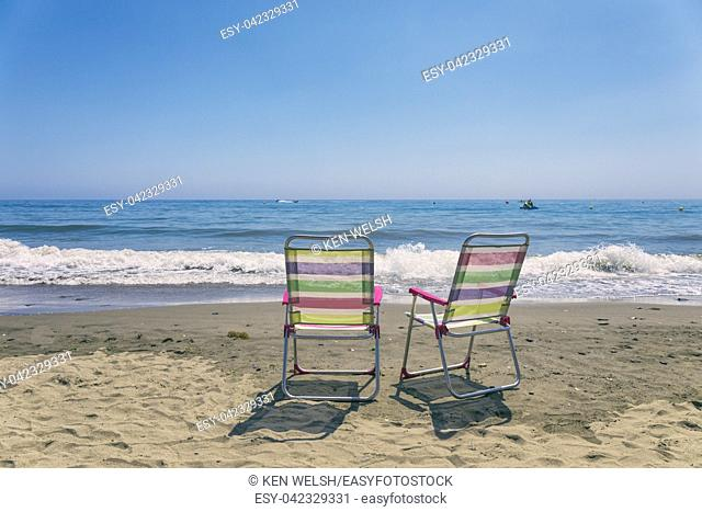 Two empty chairs on the seashore