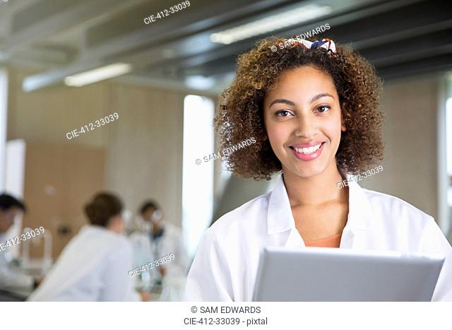 Portrait smiling college student with digital tablet in science laboratory classroom