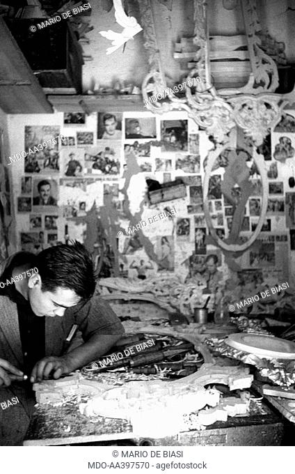 An Italian craftman carving a wooden frame. Behind him, a wall covered with newspaper clippings. Florence, 1950s
