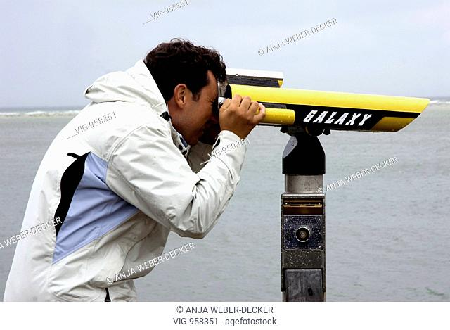 a man looks with a telescope in the wideness. - Amrum, Nordfriesland, GERMANY, 30/07/2007