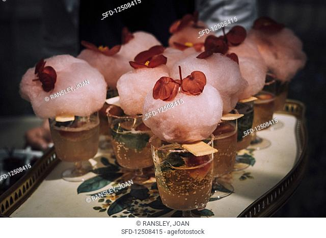 Cocktail with candyfloss and bergonia flower garnish