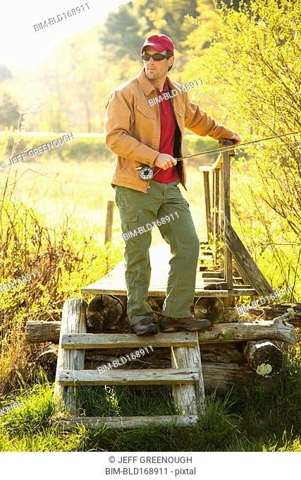 Caucasian man holding fishing pole on steps