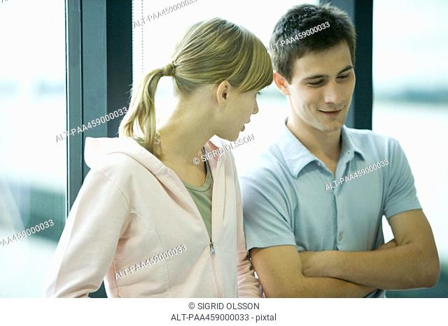 Two young friends standing in front of window, chatting, male's arms folded