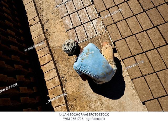 Moisés, a thirteen-year-old Salvadoran boy, molds bricks of clay at a brick factory in Istahua, El Salvador, 21 December 2013