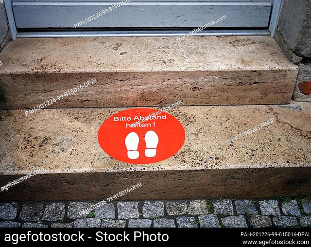 """23 December 2020, Thuringia, Weimar: A red round sticker on the stairs in front of a drugstore shows two white shoe soles and the words """"""""Please keep your..."""