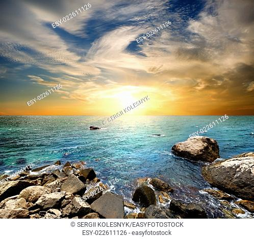 Beach at sunset, clear sea and blue cloudy sky