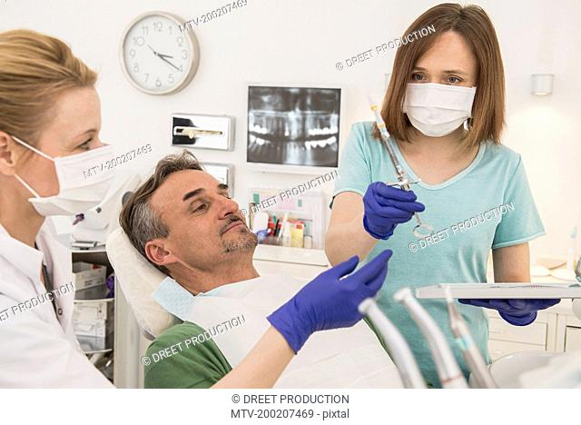 Female dentist examining patient with dental assistant, Munich, Bavaria, Germany