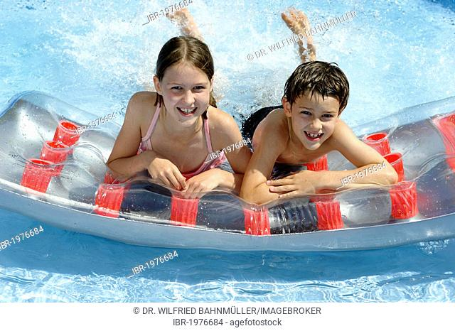 Children splashing about and swimming in a pool, water games in summer