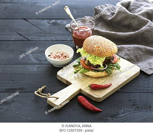 Fresh homemade burger on dark serving board with spicy tomato sauce, sea salt and herbs over dark wooden background