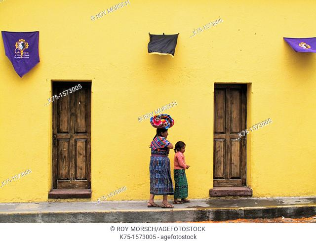 Maya mother and daughter walking on cobblestone street during Easter Week