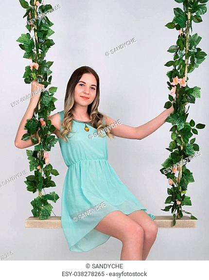 Beautiful young leggy blonde in a little green dress and gray high-heeled shoes on a swing, wooden swing suspended from a rope hemp, rope wrapped vine and ivy