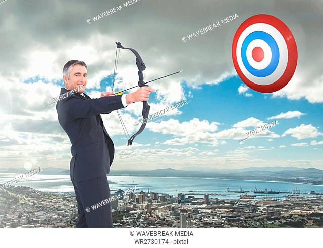 Portrait of businessman aiming with bow and arrow at target over cityscape
