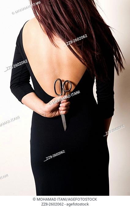 Close up of a woman holding a pair of scissors behind her back