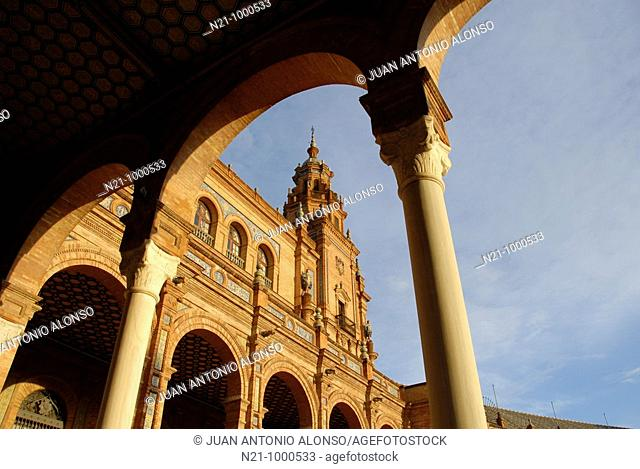 Arched galleries and one of the towers of a neo-renaissance palace in the shape of a semi-circular theatre. Plaza de España