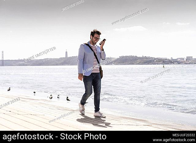 Young man walking on the waterfront using cell phone