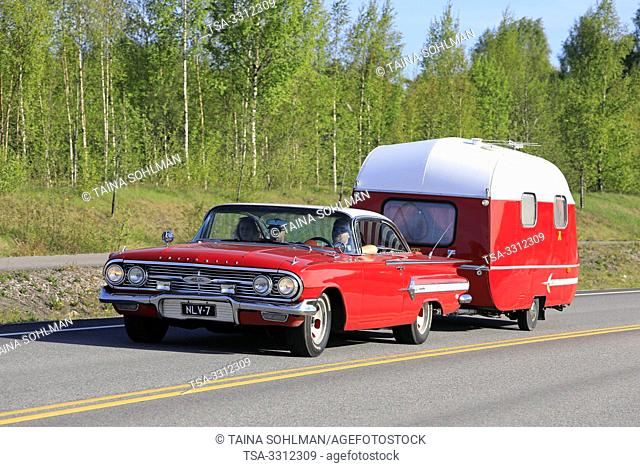 Salo, Finland. May 18, 2019. Classic 1960s red Chevrolet Impala Convertible with a matching vintage caravan on highway on Salon Maisema Cruising 2019