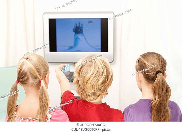 Three children watching television