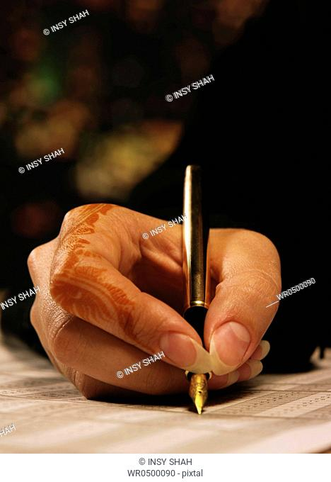 Arab Lady with henna on hands writing