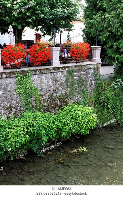 wall next to a river with many flowers