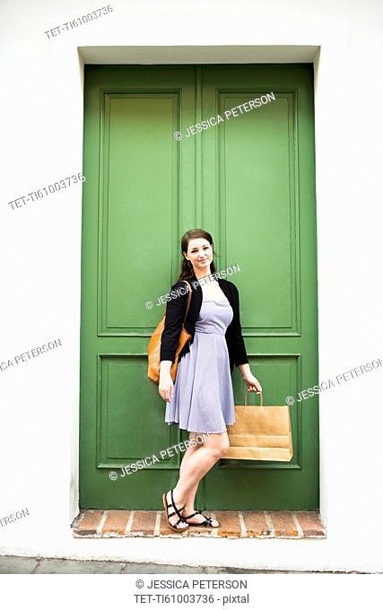 Puerto Rico, San Juan, Woman with shopping bag standing in front of green door