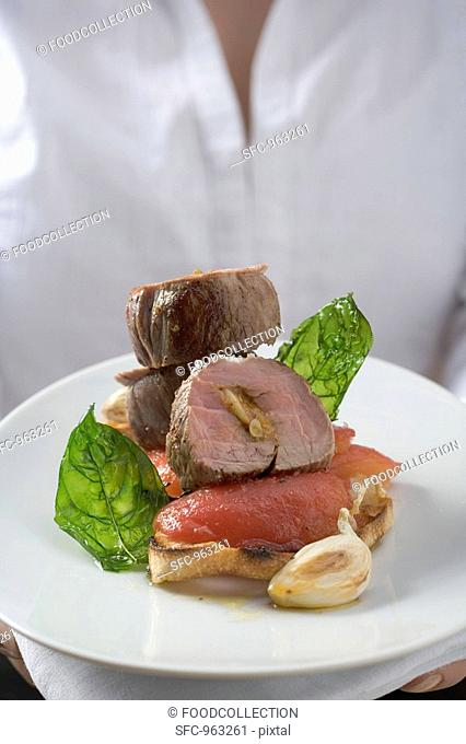 Woman serving pork fillet, tomatoes and basil on toast