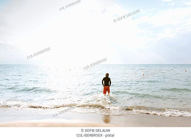 Man standing at edge of sea