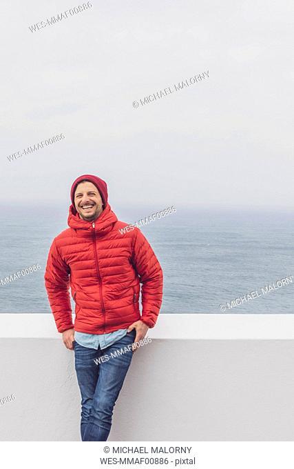 Portugal, Algarve, Sagres, Cabo de Sao Vicente, happy man standing at a wall above the sea