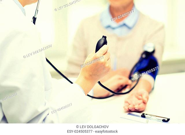 medicine, age, health care and people concept - close up of doctor with tonometer checking senior woman blood pressure level at hospital