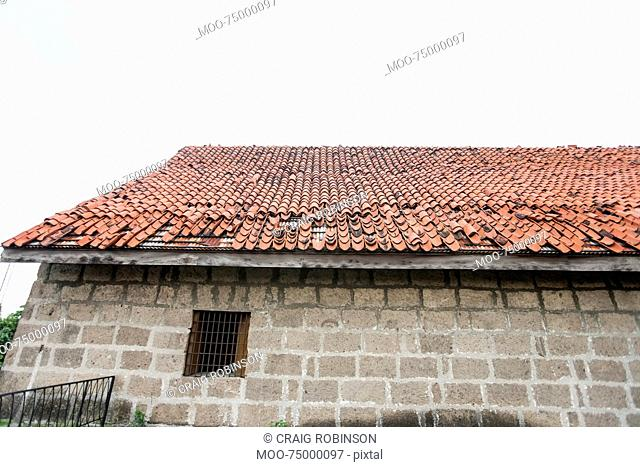 House with tiled roof and stone wall in Manila, Philippines