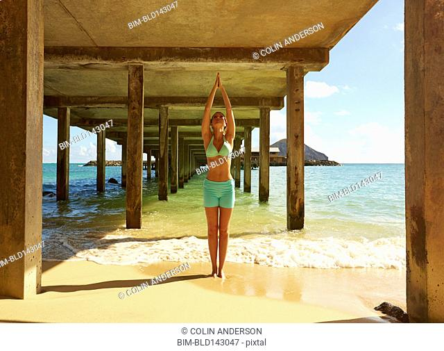 Pacific Islander woman practicing yoga under wooden pier on beach
