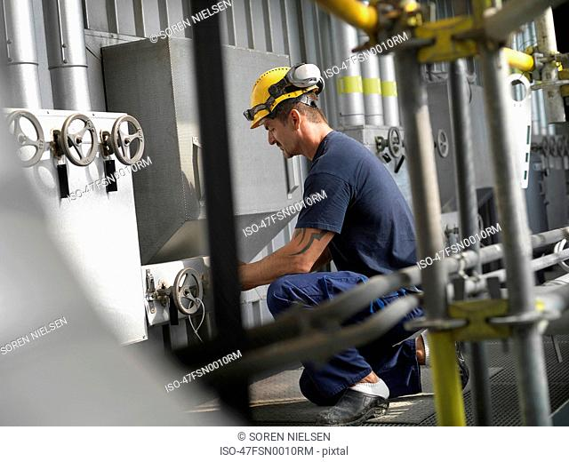 Worker operating machinery in factory