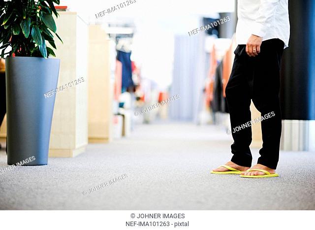 Businessman wearing flip-flops, low section