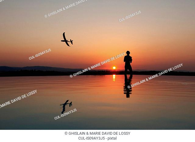 Silhouetted man flying radio controlled airplane on sunset coast, Buonconvento, Tuscany, Italy