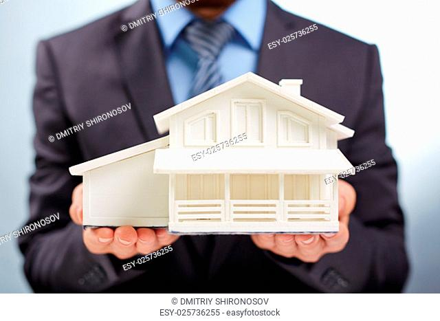 Businessman showing model of new house