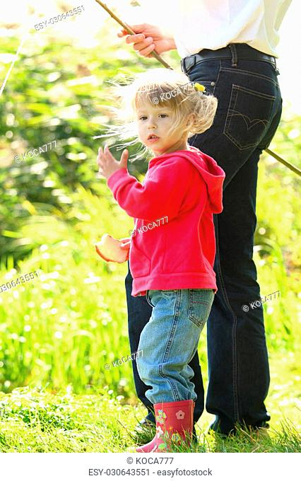 Dad and little daughter near a lake in rubber boots