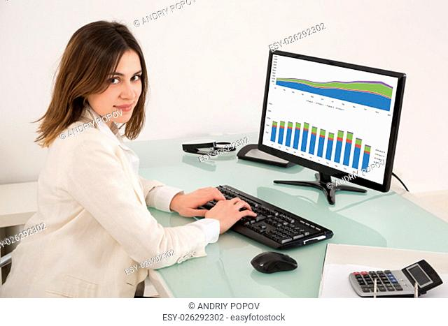 Happy Young Businesswoman Analyzing Financial Graphs On Computer