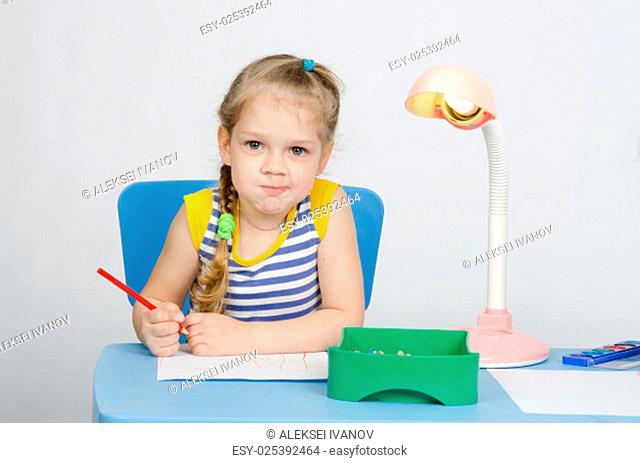 Four-year girl Europeans draws pencil on a sheet, sitting at the table