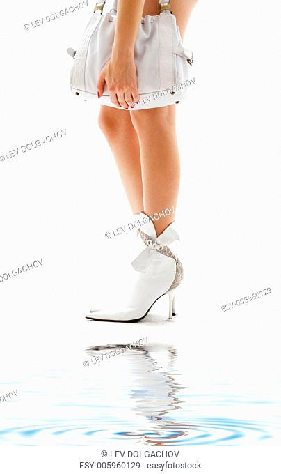 closeup of beautiful legs in white boots with purse