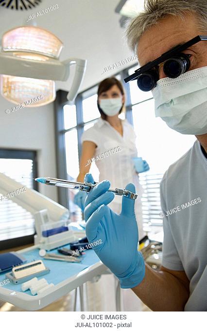 Dentist holding syringe in dentist's office