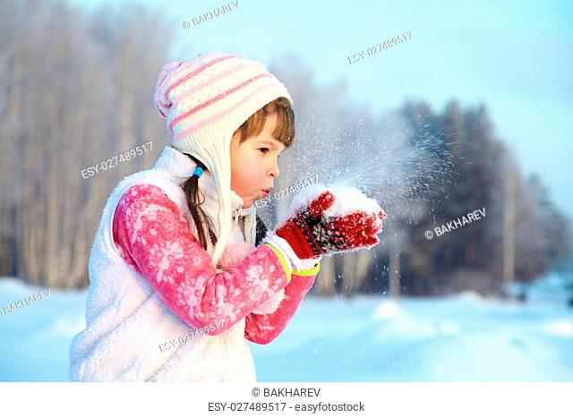portrait of a girl walking around outdoors in the winter, blowing on snow