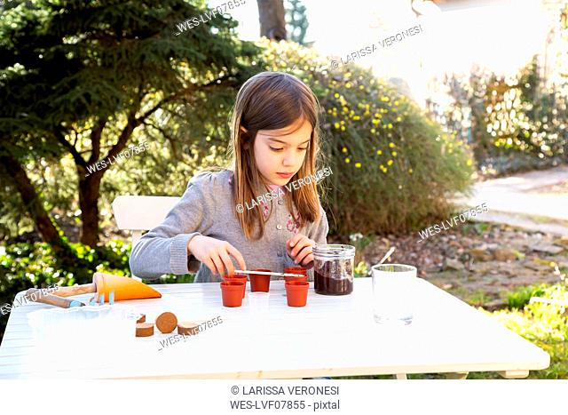 Portrait of little girl at garden table sowing seeds