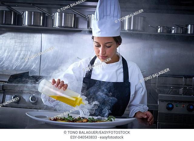 Chef woman working in kitchen with smoke and oil