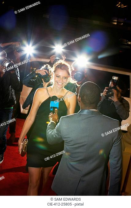 Celebrity being interviewed and photographed by paparazzi at event